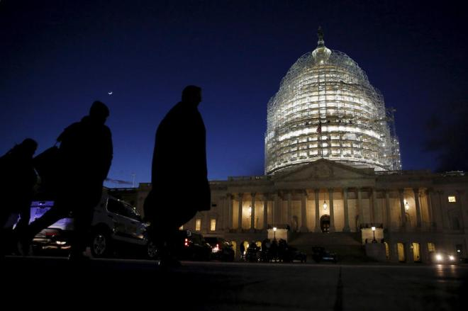 People walk past the U.S. Capitol dome in the hours before Obama delivers the State of the Union address to a joint session of Congress in Washington
